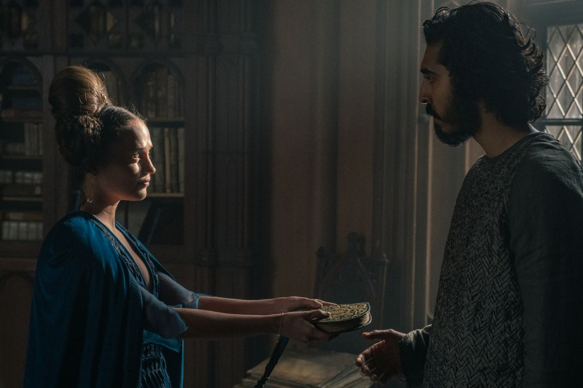 Alicia Vikander and Dev Patel in a library. She's giving him a book.