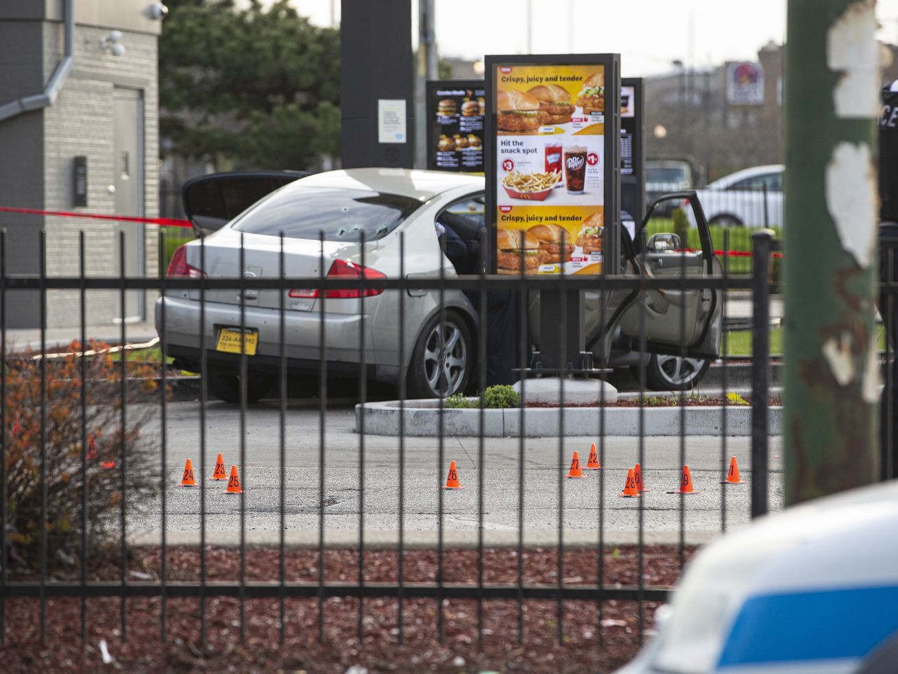 Shell casings litter the scene at a McDonald's parking lot Sunday afternoon where a 7-year-old girl was shot and killed and her father was seriously wounded as they waited in a drive-thru.