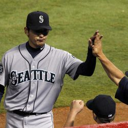 Seattle Mariners' Hisashi Iwakuma, center, of Japan is greeted back at the dugout after being pulled in the sixth inning of a baseball game against the Texas Rangers Friday, Sept. 14, 2012, in Arlington, Texas.