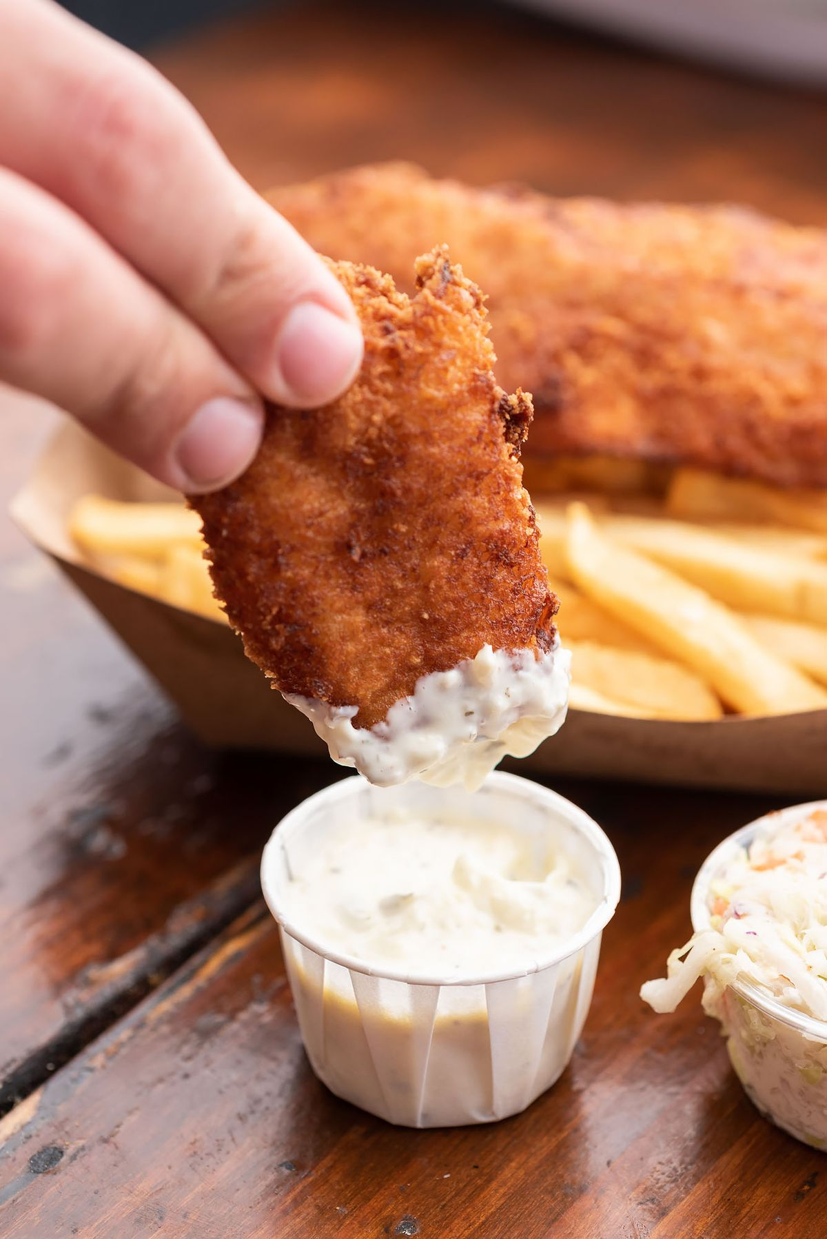 Dunking fried fish in tartar sauce on a wooden table.