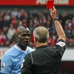 Manchester City's Mario Balotelli, left, is shown a red card by referee Martin Atkinson after being shown a 2nd yellow card during their English Premier League soccer match against Arsenal at the Emirates stadium, London, Sunday, April 8 , 2012.