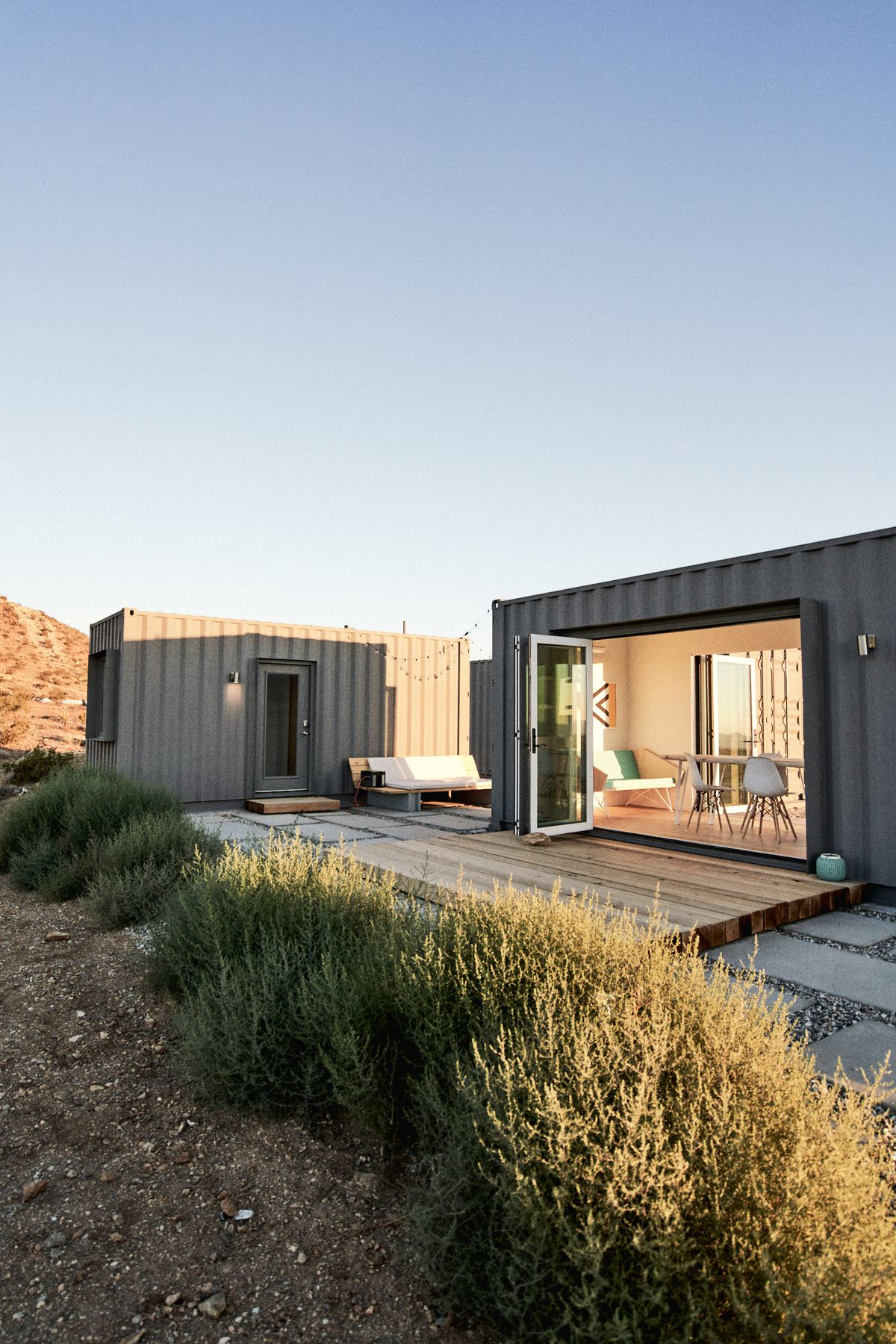 A sunset view of two shipping container houses, one in the background and another with sliding glass doors that open onto a cedar deck.