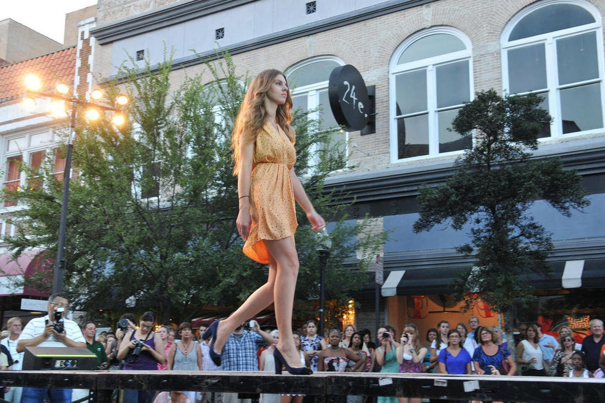A model struts along the catwalk located on Broughton Street in front of 24e Thursday evening Sept. 6, 2012 during Savannah's Second Fashion's Night Out in Savannah, Ga. Clothing from local retailers in the downtown area was highlighted during the event.