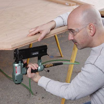 Person applying glue to the side of the poker table.
