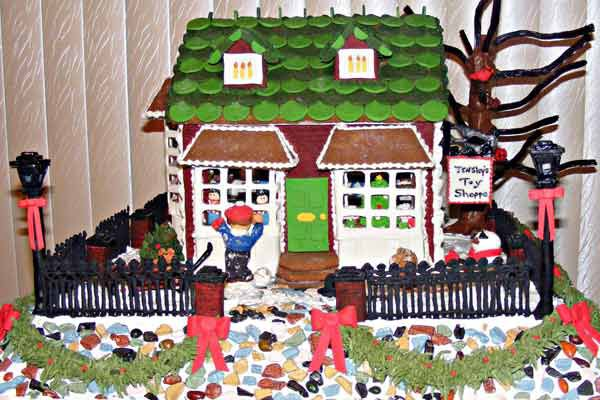 Gingerbread toy shop with a black fence surrounding it.