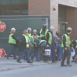Construction workers entering and leaving, in the left field corner, having their bags/buckets inspected by Cubs Security