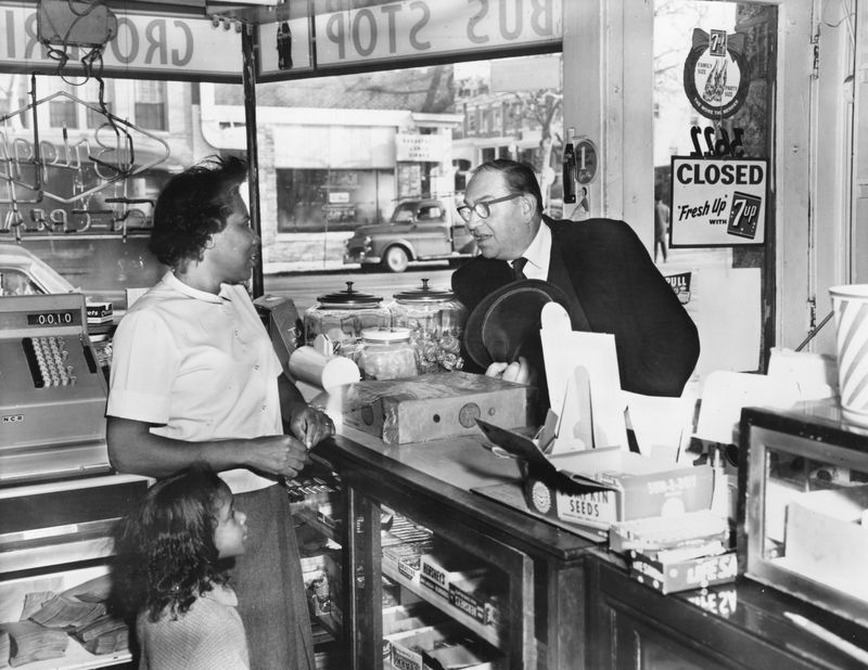 A Black business owner and a white customer on opposite sides of a shop counter in 1965.