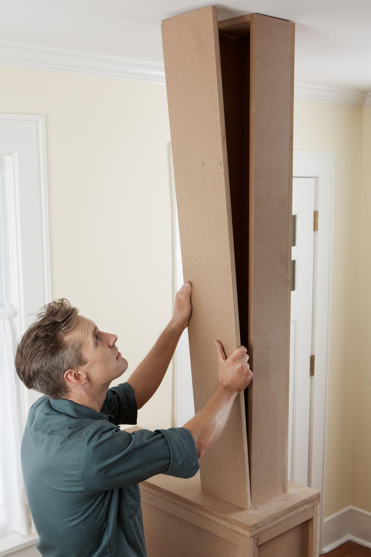 Man Assembles Column Of Room Divider
