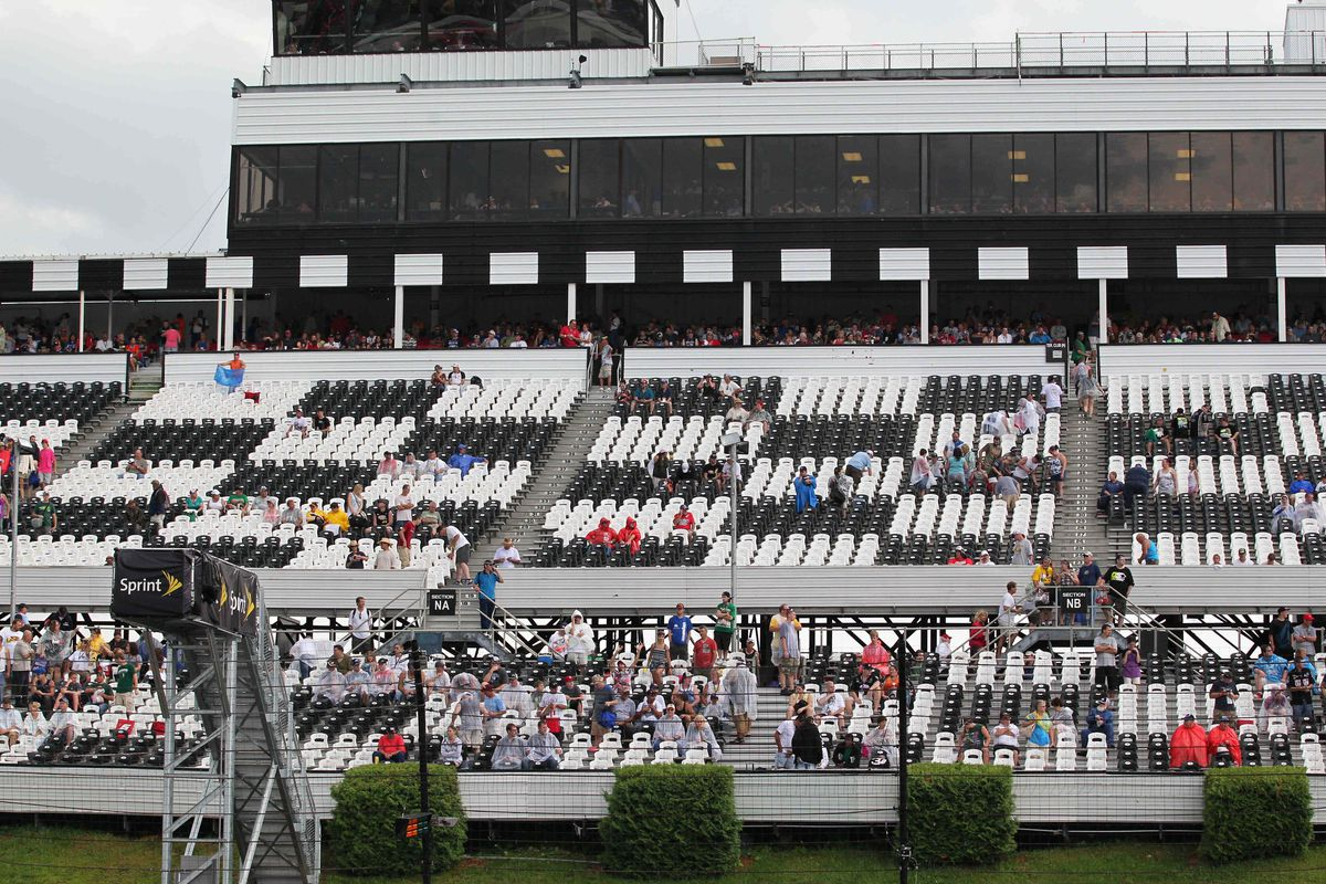 Aug 5, 2012; Long Pond, PA, USA;   Fans take cover during a rain delay before the start of the NASCAR Sprint Cup Series  Pennsylvania 400 at Pocono Raceway.  Mandatory Credit: Anthony Gruppuso-US PRESSWIRE