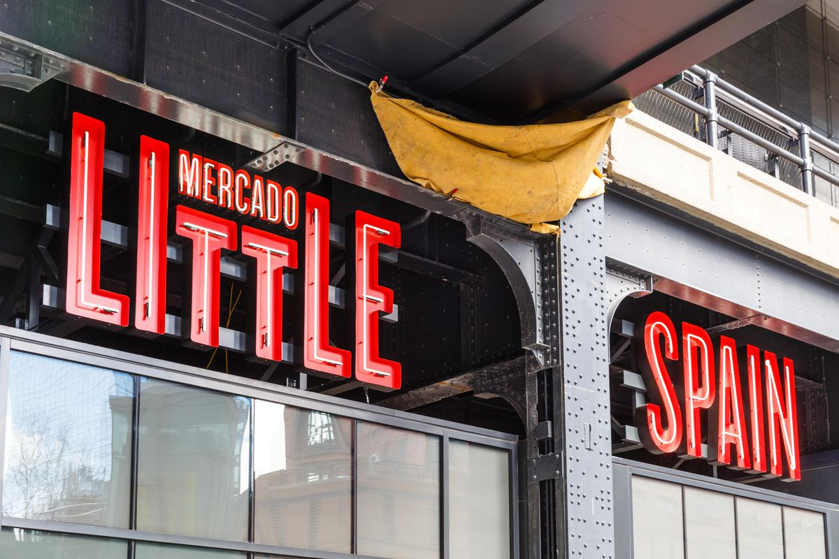 The exterior of Mercado Little Spain with red lettering and large windows