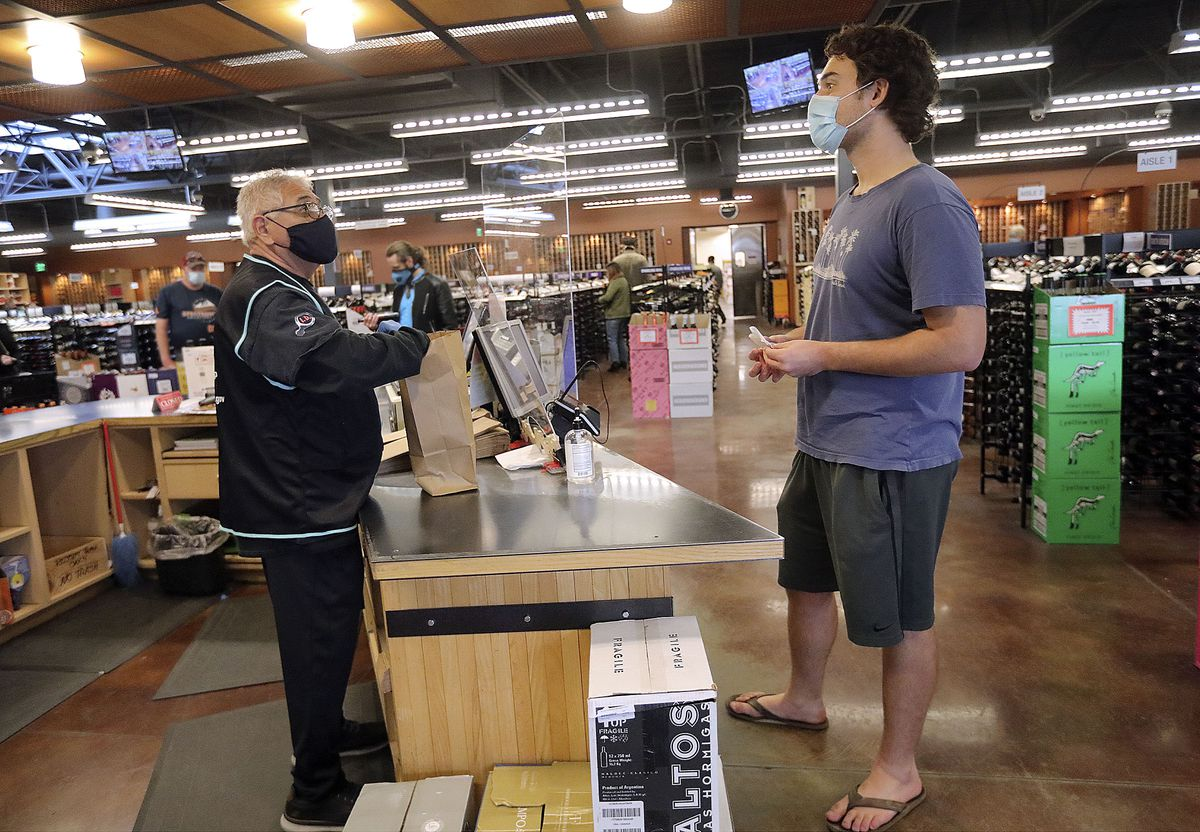 Freddie Rico rings up Sam Tyler at a state liquor store in Salt Lake City on Friday, Oct. 23, 2020.