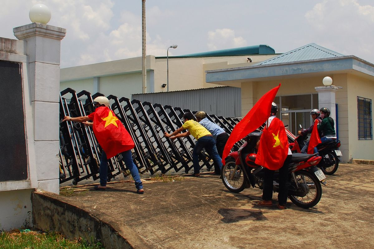 In this picture taken on May 14, 2014, protesters holding Vietnamese flags attempt to push down the front gate of a factory in Bien Hoa, Dong Nai province, as anti-China demonstrations on May 15 spread to 22 Vietnamese provinces.