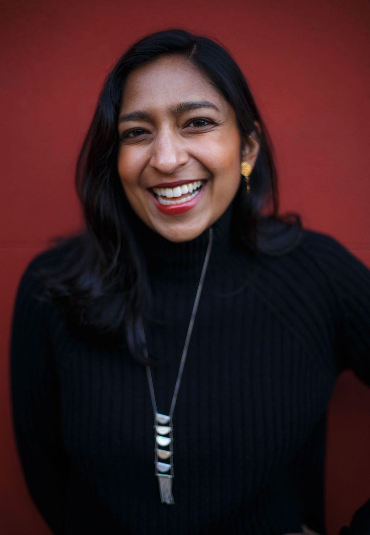 A smiling woman, Priya Krishna, wearing a black turtleneck and standing in front of a red wall.