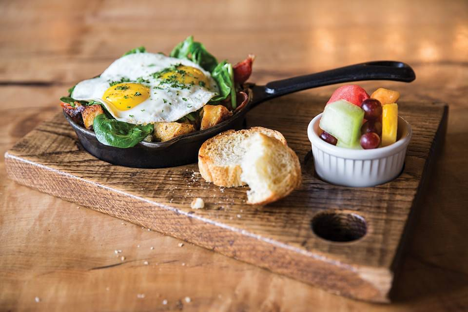 Skillet hash on a serving board with bread and fruit