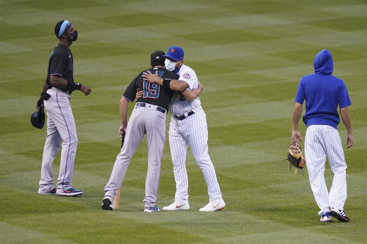 New York Mets left fielder Dominic Smith (2) and Miami Marlins shortstop Miguel Rojas (19) hug in center field before both teams walk off in protest at the start of their baseball game on August 27.