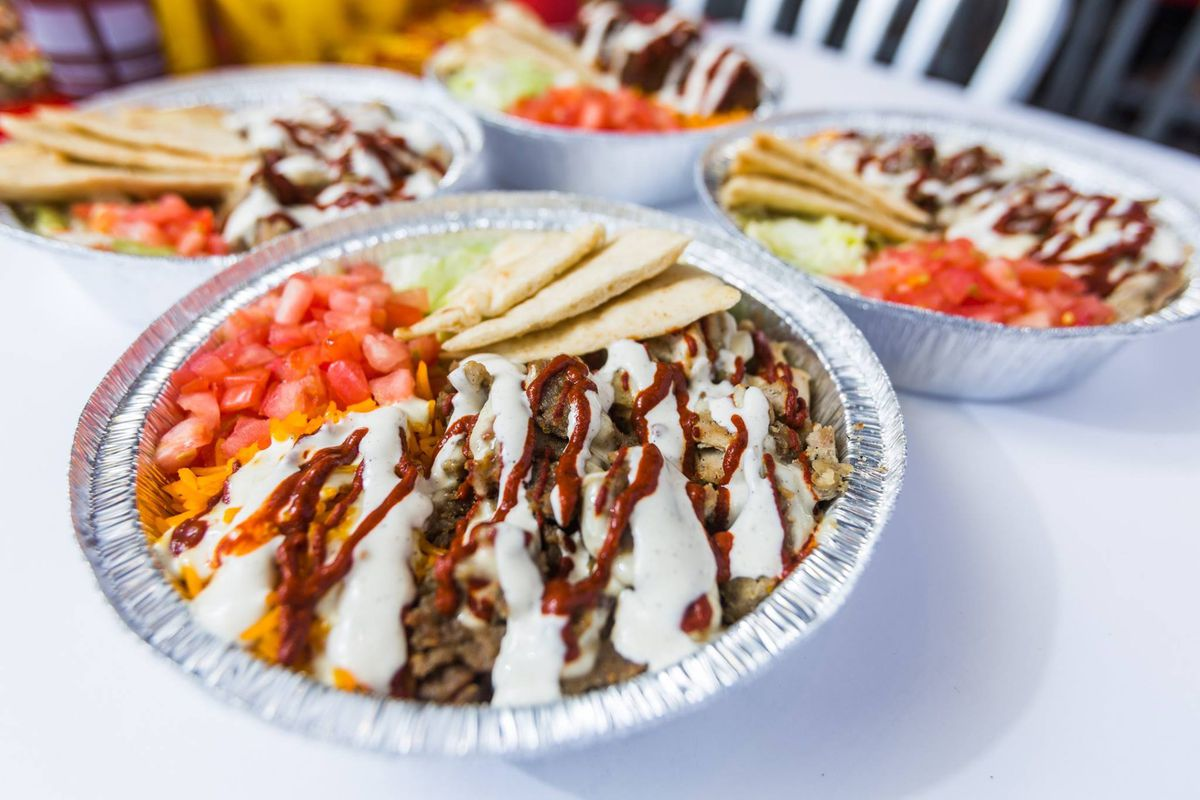 A foil bowl full of gyros and drizzle with white and red sauces.