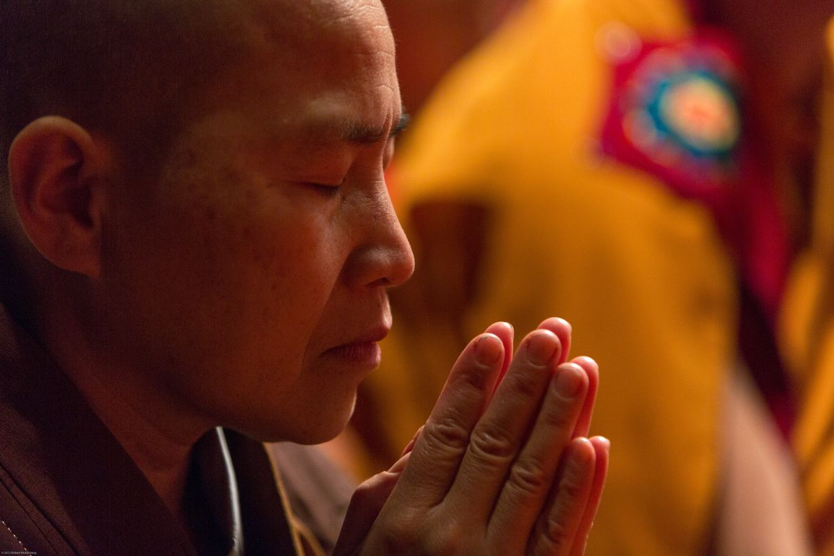 A Japanese female monk prays while attending the Dalai Lama teachings at the Beacon Theater October 19, 2013 in New York City.