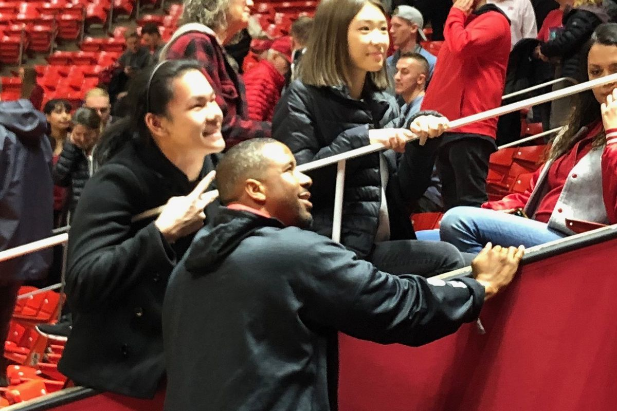 Former University of Utah star Andre Miller takes time to pose for a photo with Ute fans after watching Saturday's game against Nevada at the Huntsman Center.