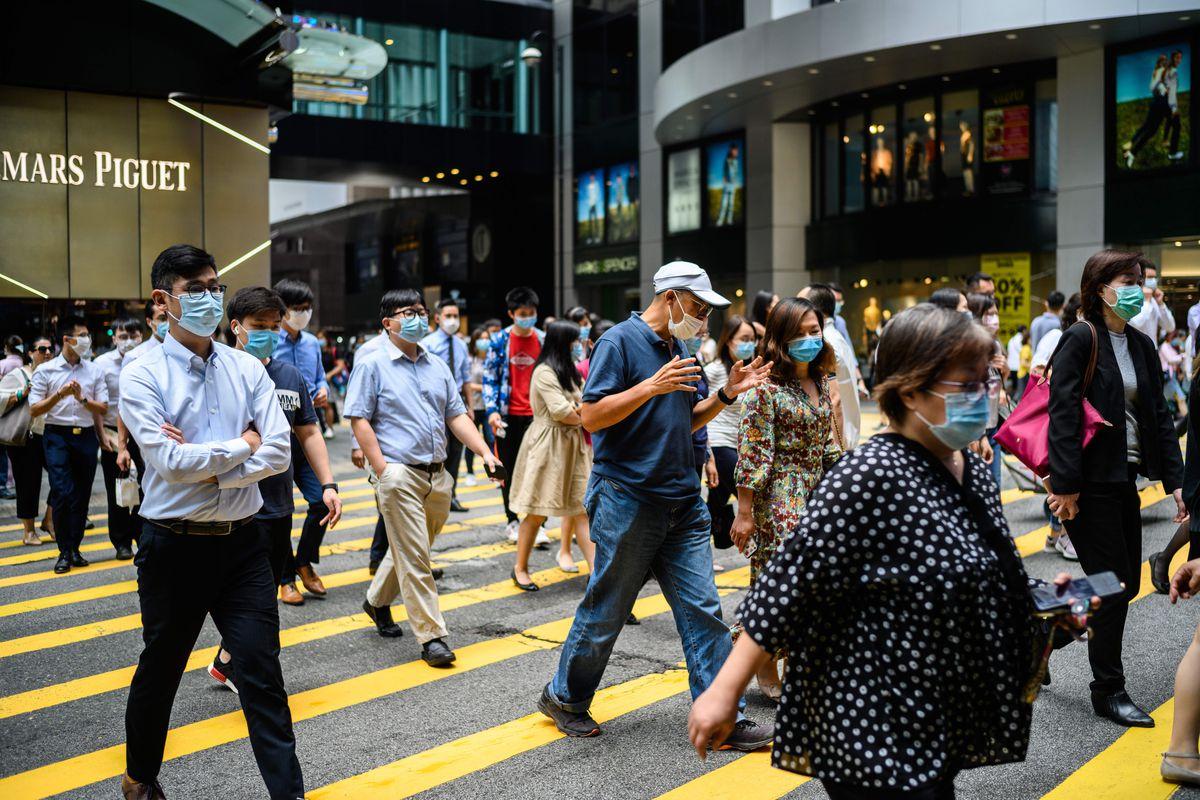 Pedestrians in Hong Kong wear face masks