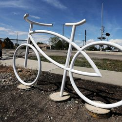 Arianne Araujo and her son Miguel pass by a ghost bike memorial in honor of Douglas Crow in Provo, Wednesday, May 20, 2015. Crow was an avid cyclist who died Feb. 13, 2013.