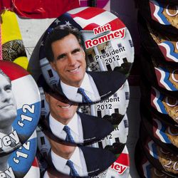 Buttons showing the likeness of Republican presidential candidate, former Massachusetts Gov. Mitt Romney, are seen at a vendor stand outside a Romney campaign event at an oil company in Milwaukee, Monday, April 2, 2012.