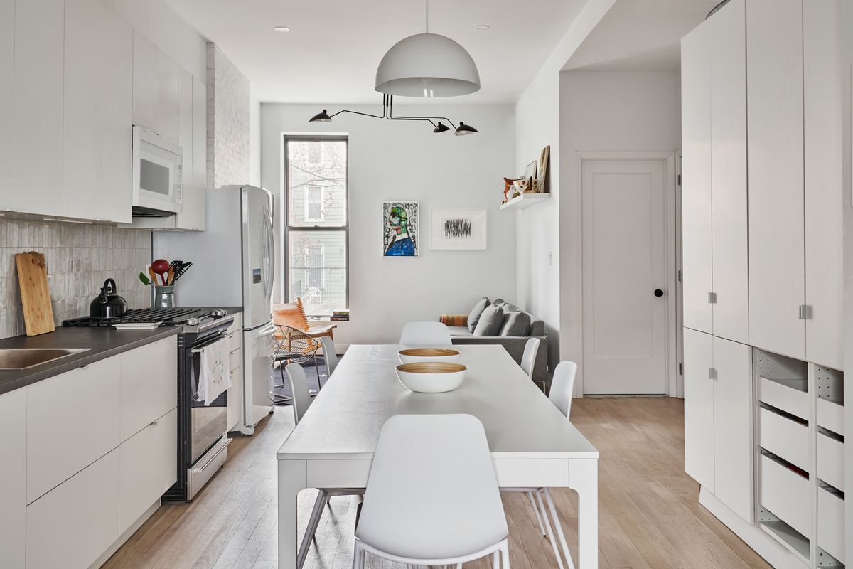A kitchen with white cabinetry and a dining table in the middle.