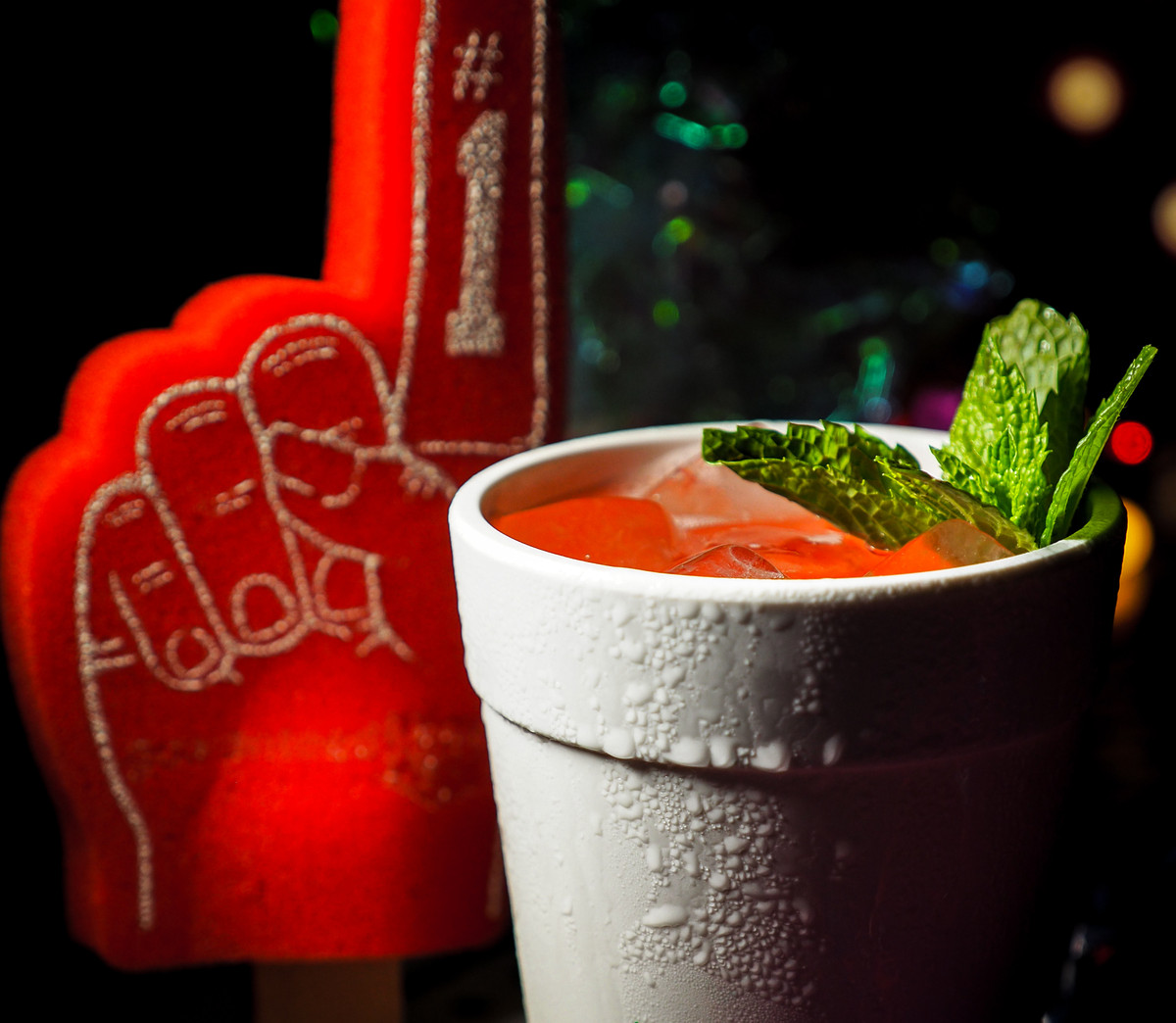 A pink drink garnished with mint in a styrofoam cup, with a giant red foam fan finger on the left.