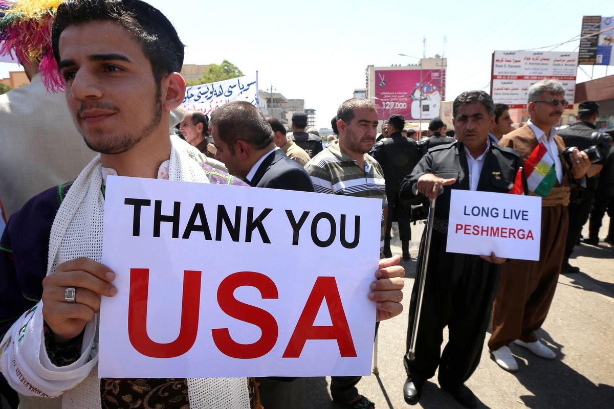 Iraqi Kurds and Christians hold up signs thanking the US in Erbil