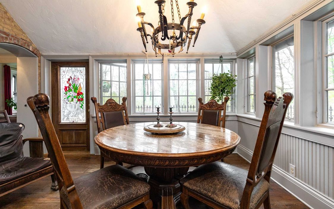 A four-person wood dining room table has a gothic looking chandelier above it.