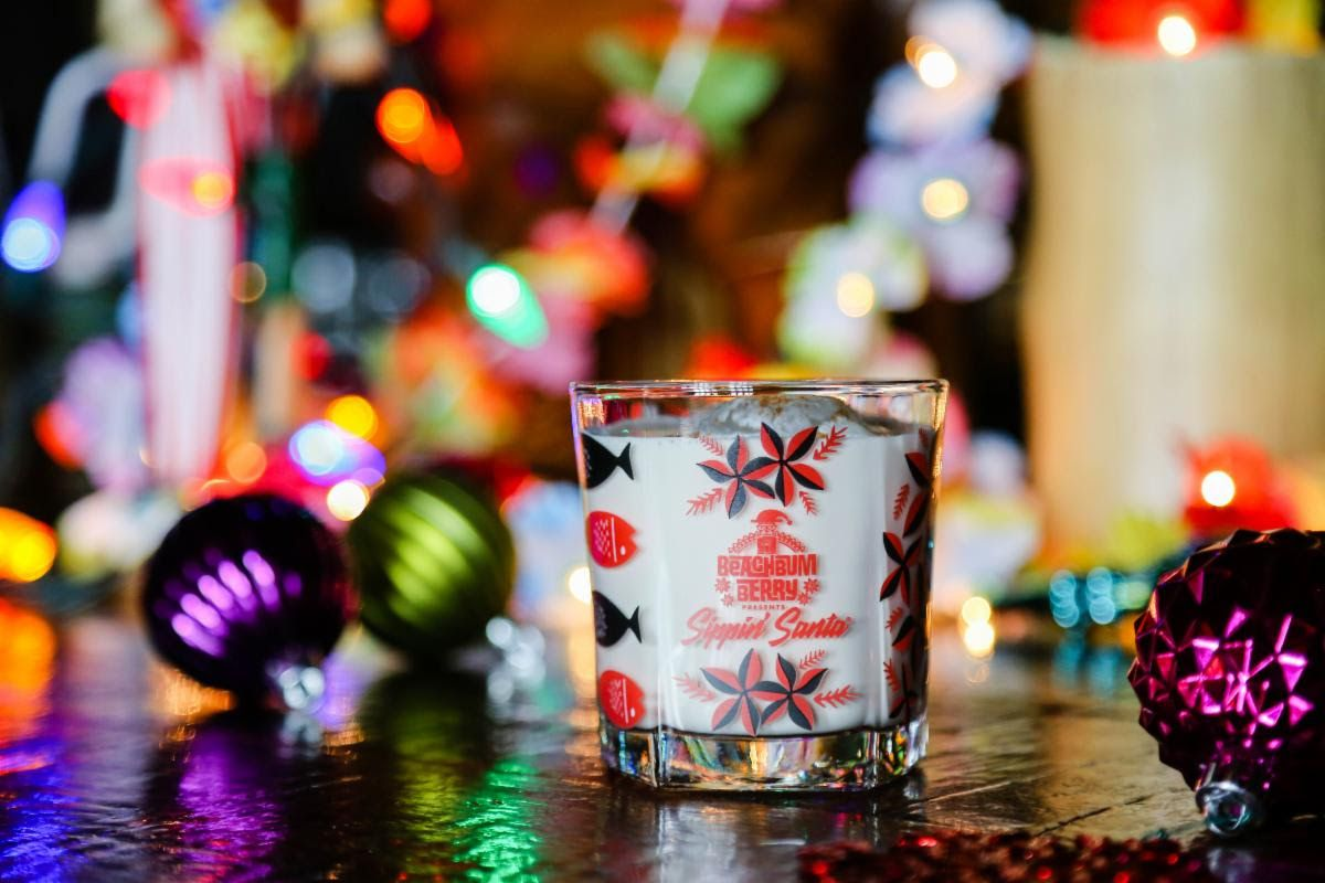 A white cocktail in a glass with lots of Christmas decorations.
