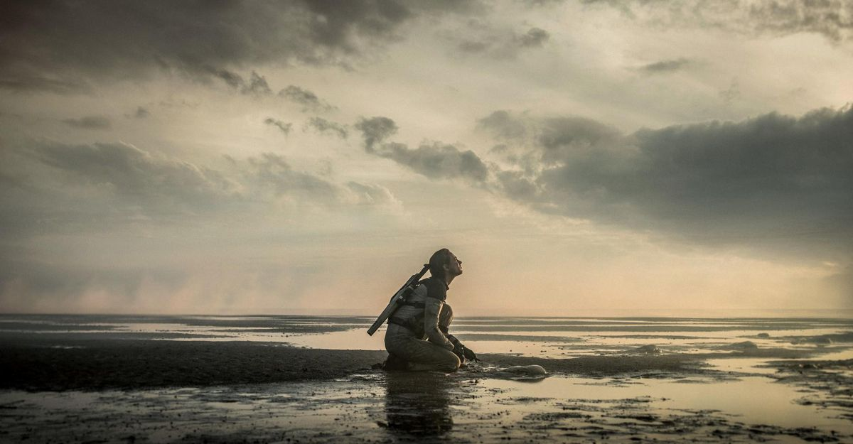 A lone woman with a rifle kneels on a placid, alien-looking shore