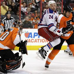 New York Rangers' Ryan Callahan, center, leaps against the back of Philadelphia Flyers' Pavel Kubina, right, as the puck shoots past the shoulder of Flyers goalie Ilya Bryzgalov, but not into the net, during the first period of an NHL hockey game, Tuesday, April 3, 2012, in Philadelphia.