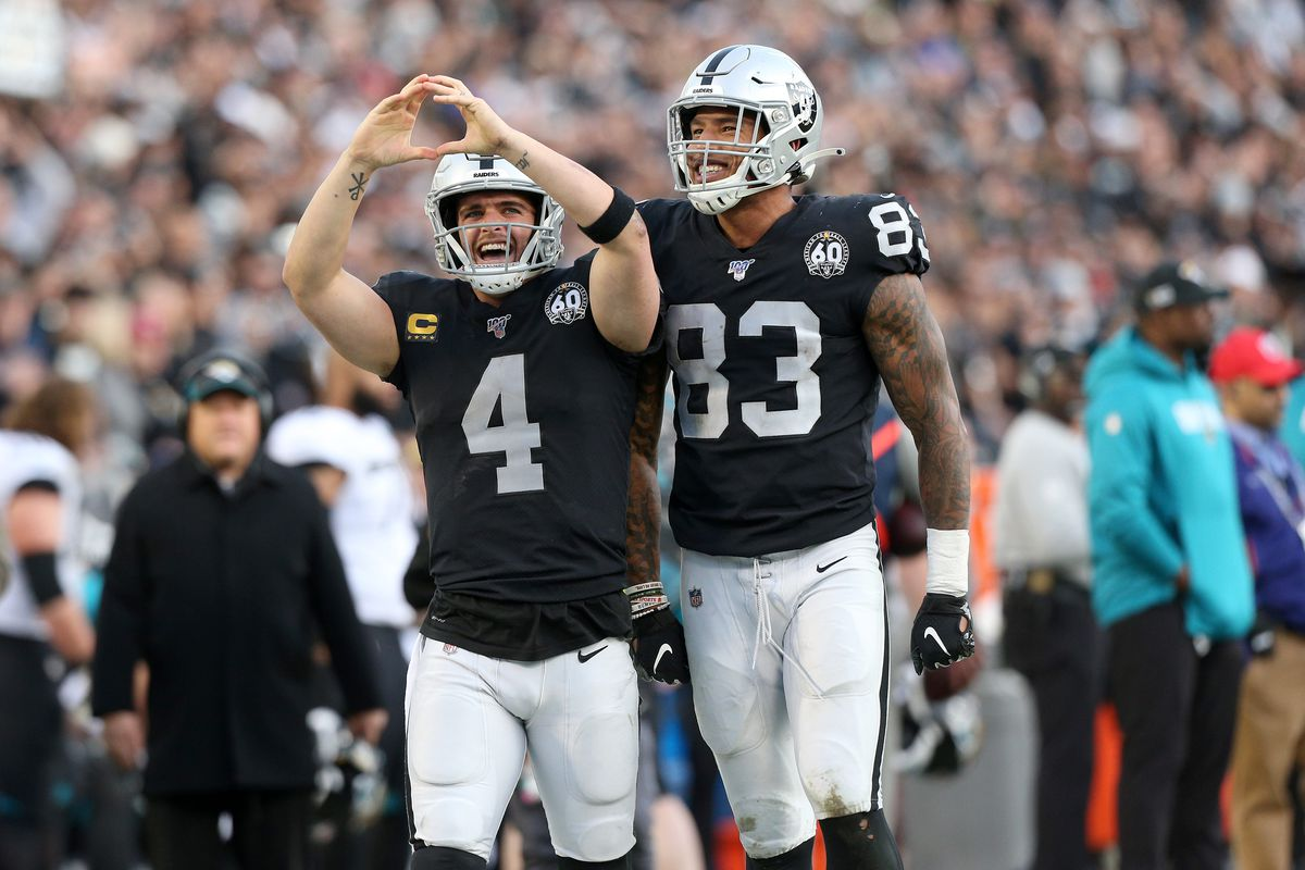 Oakland Raiders quarterback Derek Carr celebrates next to tight end Darren Waller after rushing for a first down against the Jacksonville Jaguars in the fourth quarter at Oakland Coliseum.