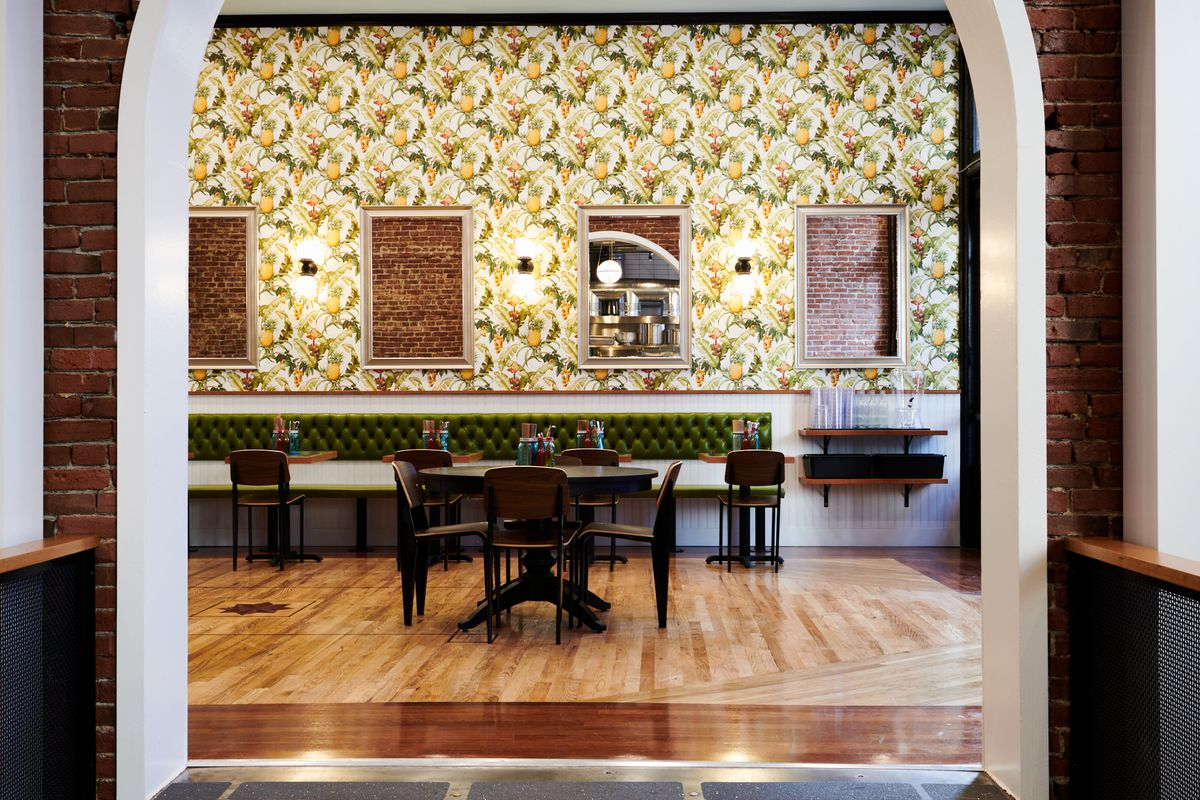 Through an archway, Bae's Chicken's front room leads into a dining room, with pineapple wallpaper and mirrors reflecting the unfinished brick