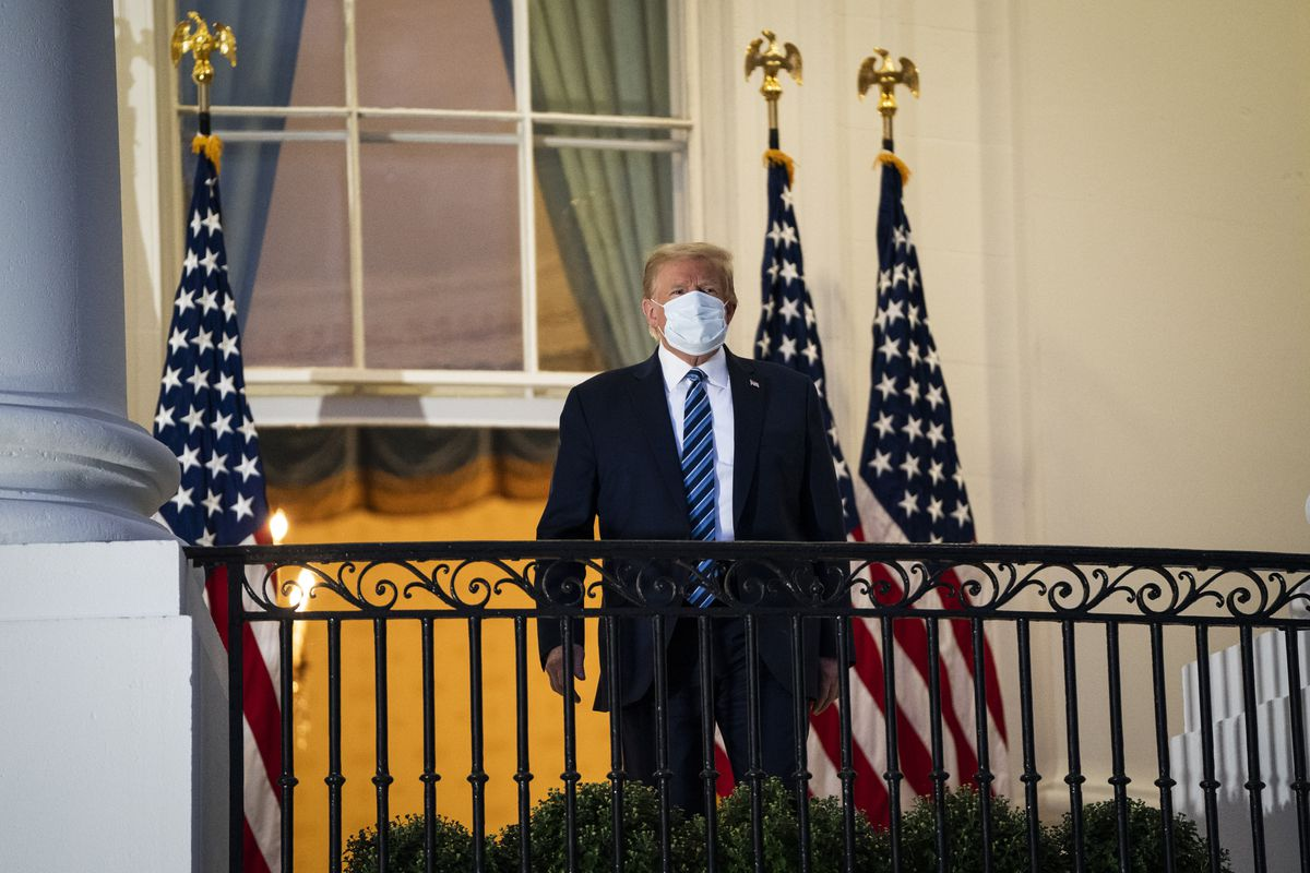 President Donald Trump standing on a White House balcony wearing a face mask