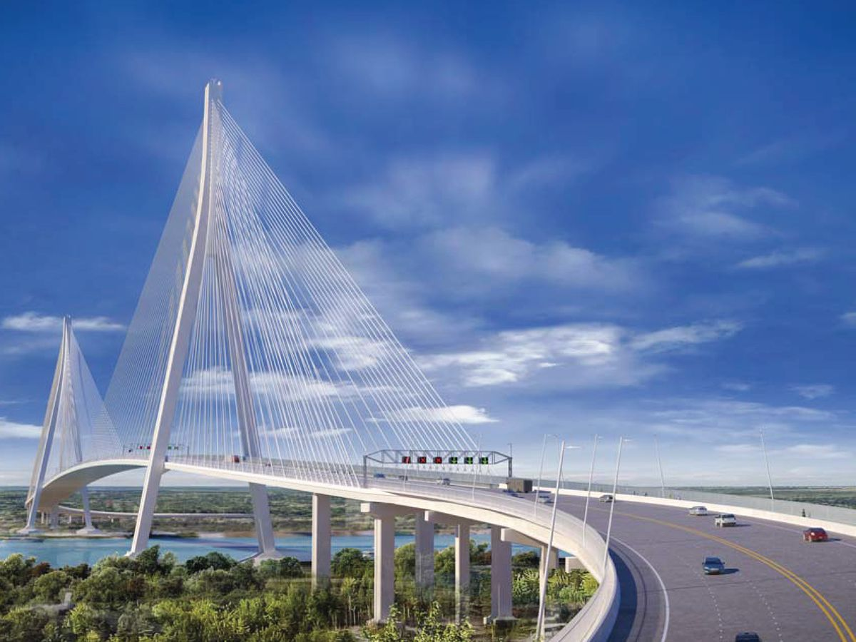 The Gordie Howe International Bridge which is a curved suspension bridge with angled arches and a multitude of metallic cables. The bridge stretches out over trees and a body of water.