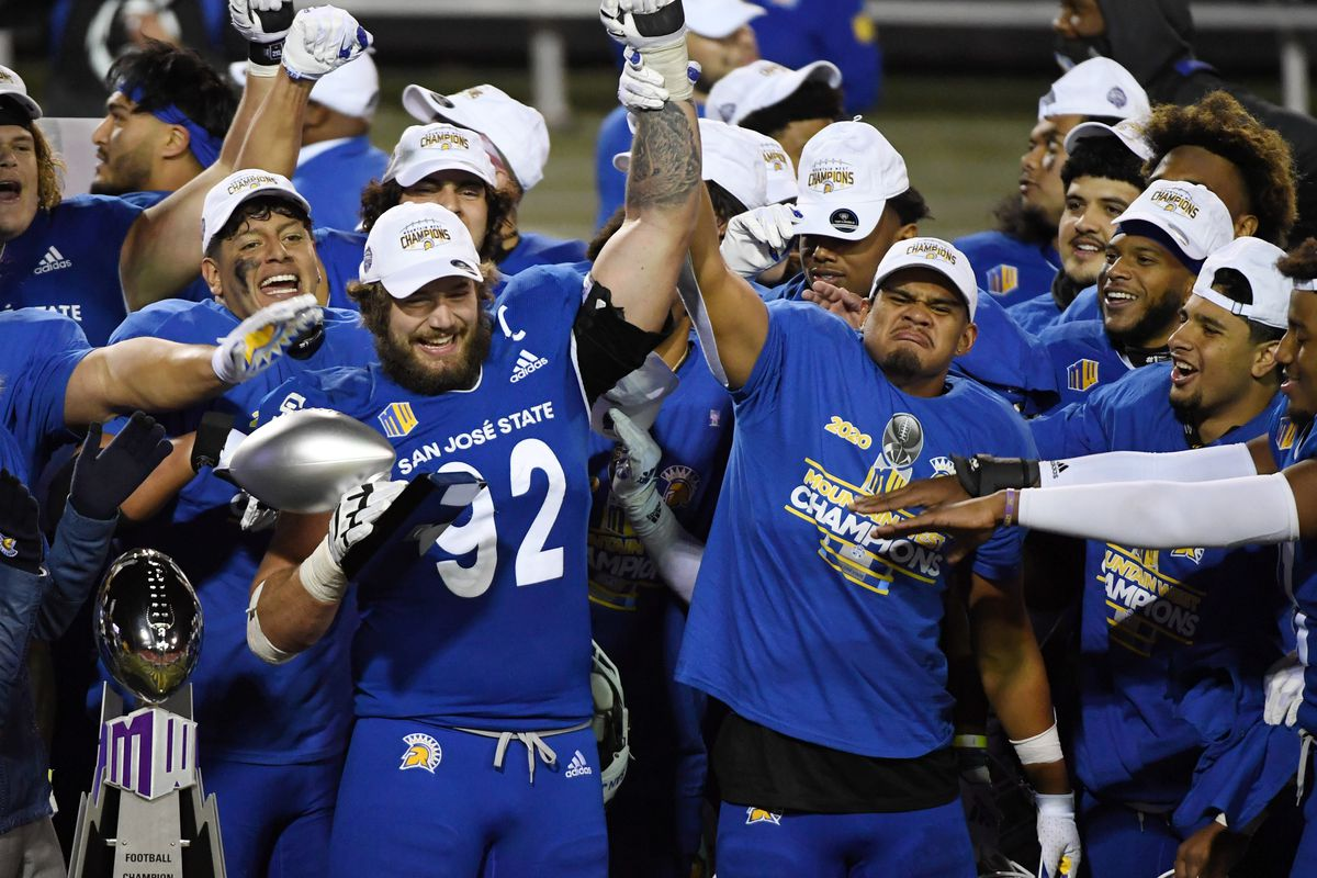 Linebacker Isa'ako Togia (R) #40 of the San Jose State Spartans holds up the arm of defensive lineman Cade Hall #92 as he lifts up the the Mountain West Championship game defensive MVP trophy after the team defeated the Boise State Broncos 34-20 to win the Mountain West Football Championship at Sam Boyd Stadium on December 19, 2020 in Las Vegas, Nevada.