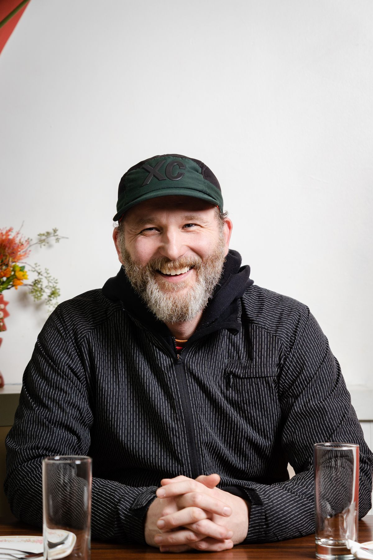 Eric Nelson, a co-owner of Eem, smiles as he sits at a table holding his hands. He's a bearded man wearing a zip-up hoodie and a green cap.