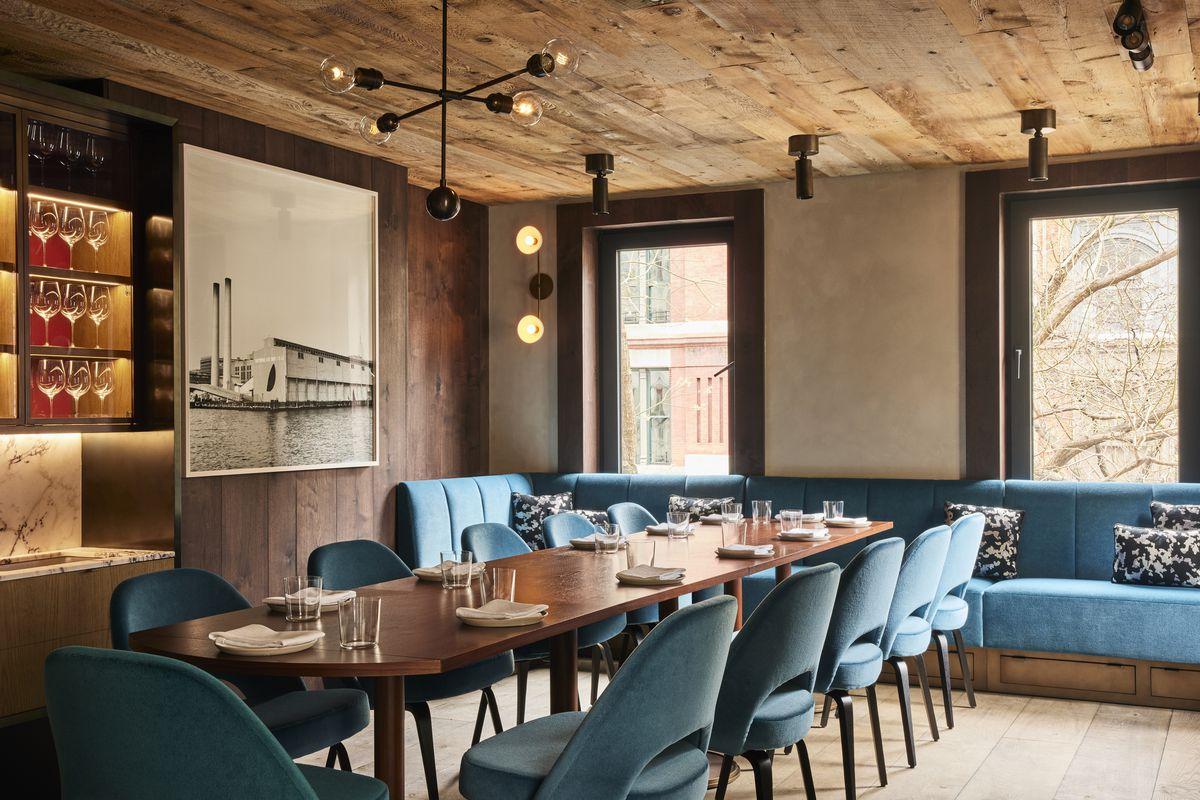 A chic, upstairs dining room with a lengthy communal table, custom light fixtures on the ceiling, and windows that look out over a New York City street