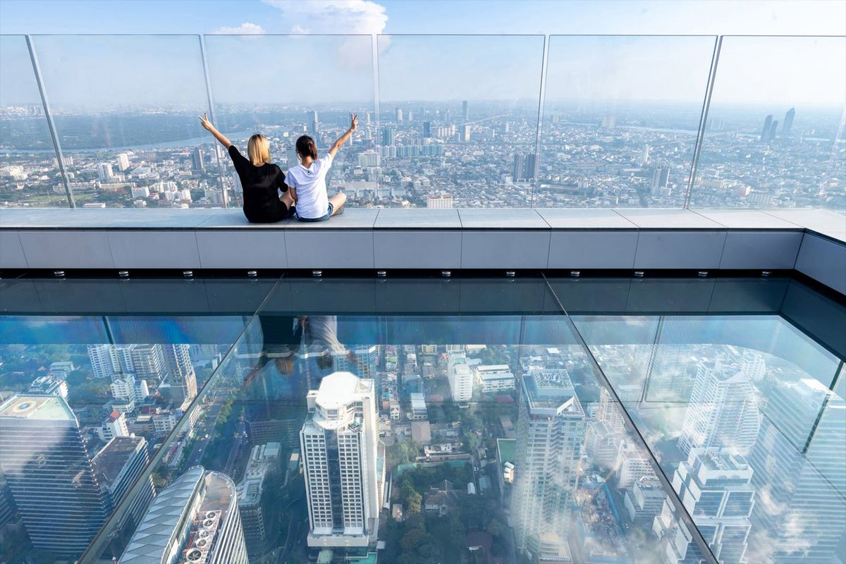 Two people sitting on glass observation deck