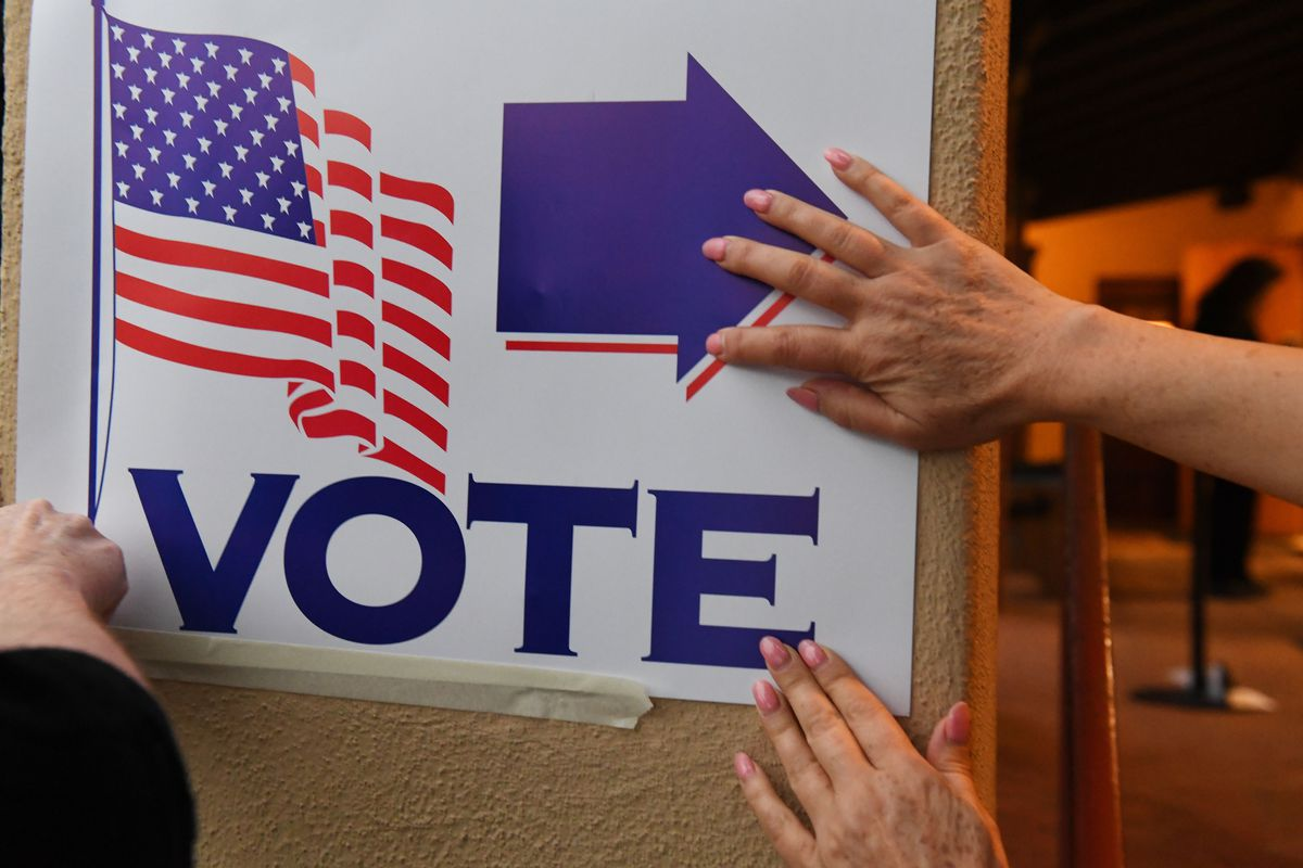 """Poll workers in 2018 attach a """"VOTE"""" sign as they set up a polling station at Laguna Beach City Hall in California."""