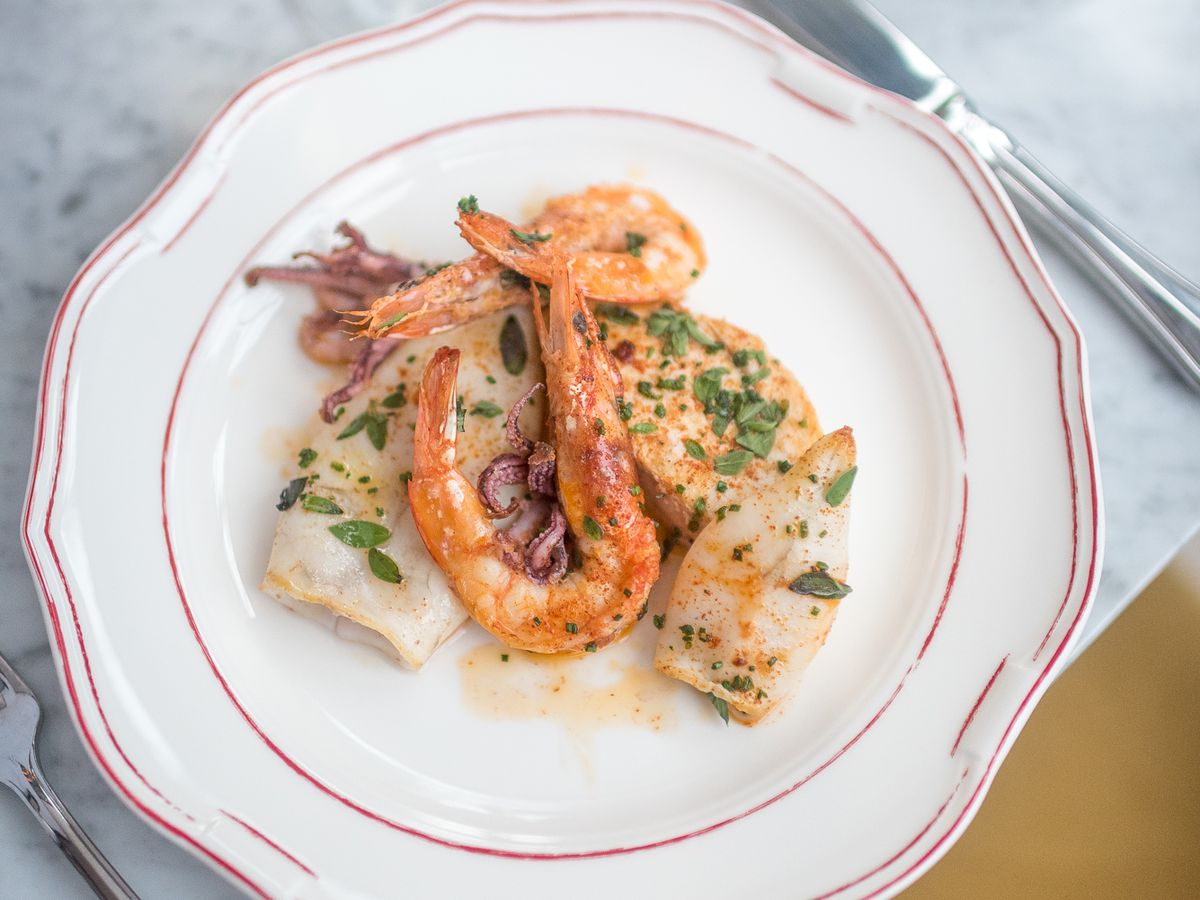 A grilled shrimp is surrounded by squid and fish on a white plate.