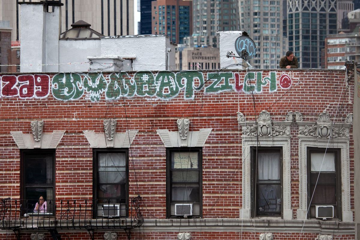 People enjoy the view from their Chinatown building while social distancing.