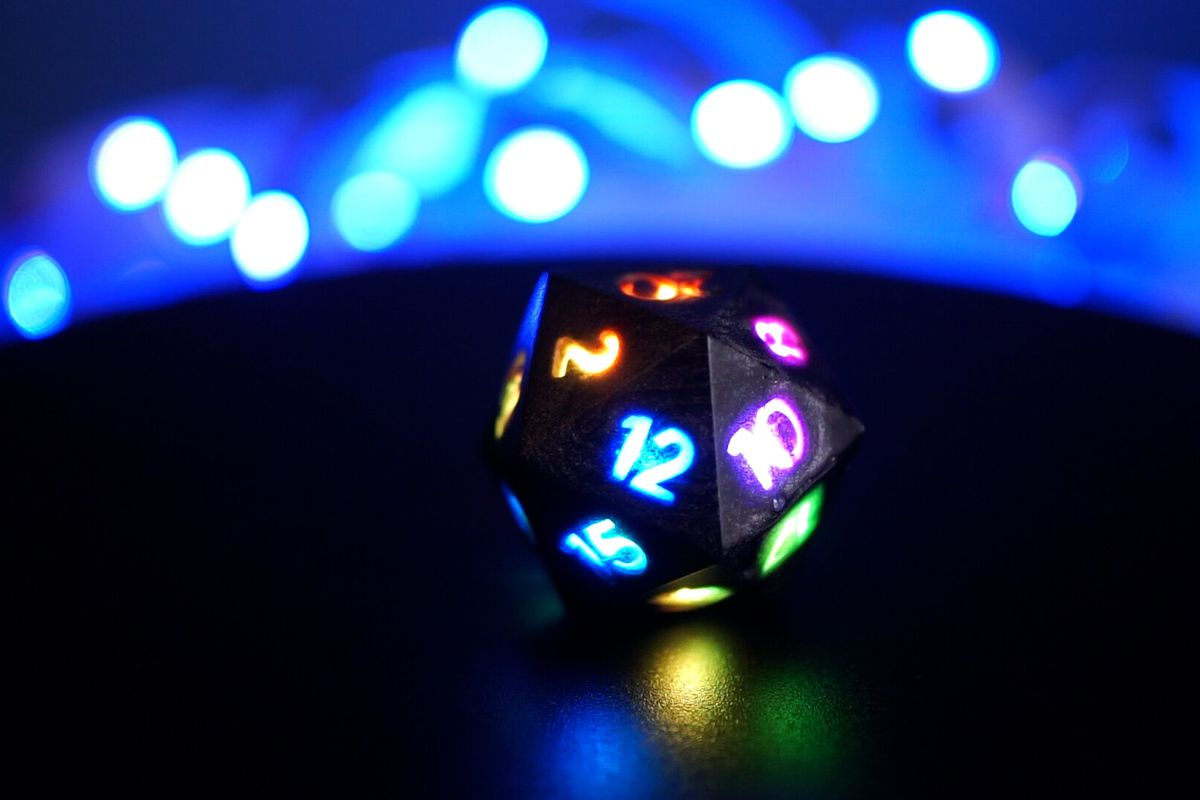 A black die with rainbow LED numbers in front of a blue background.