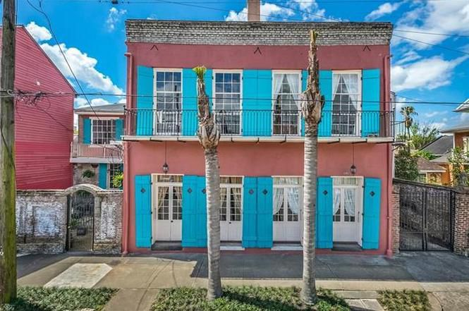 The exterior of 1208 Ursulines Avenue in New Orleans. The facade is red with blue shutters and a balcony on the upper level. There is a flat roof.