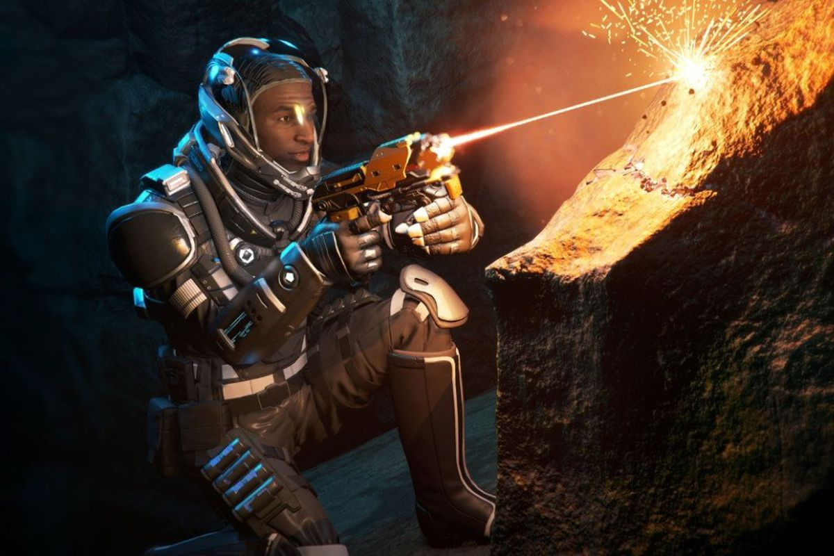 A player avatar takes a knee inside a cave system, aiming a mining tool at a rock outcrop in the alpha 3.7 update for the Star Citizen persistent universe game.