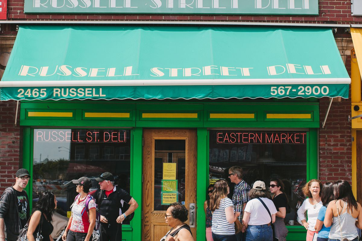 Customers gather outside of Russell Street Deli underneath bright green awnings on a sunny day at Eastern Market in Detroit.