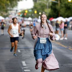 Savana Lee, of Provo, wears a pioneer costume as she competes in theDeseret News 10K in Salt Lake City on Friday, July 23, 2021.