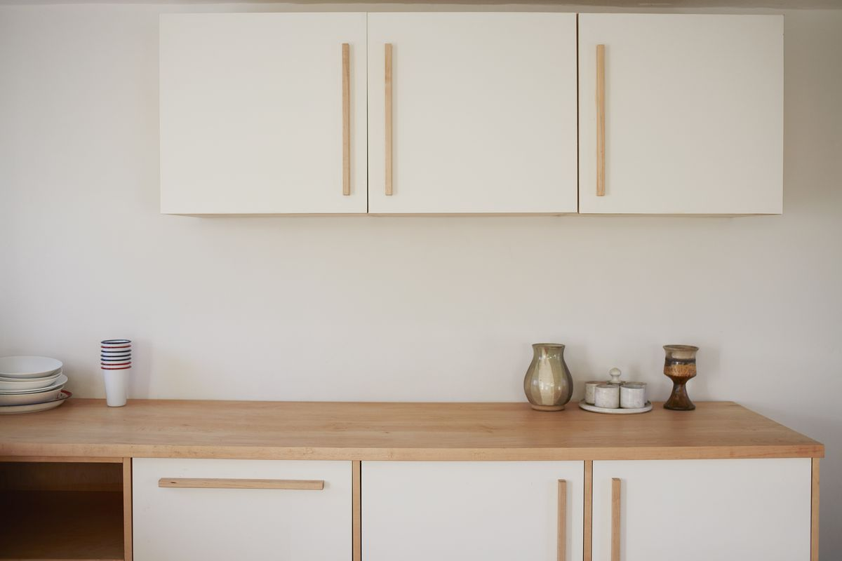 A new minimalist kitchen, white and natural wood cabinets, some cups and bowls placed on the natural wood countertop.