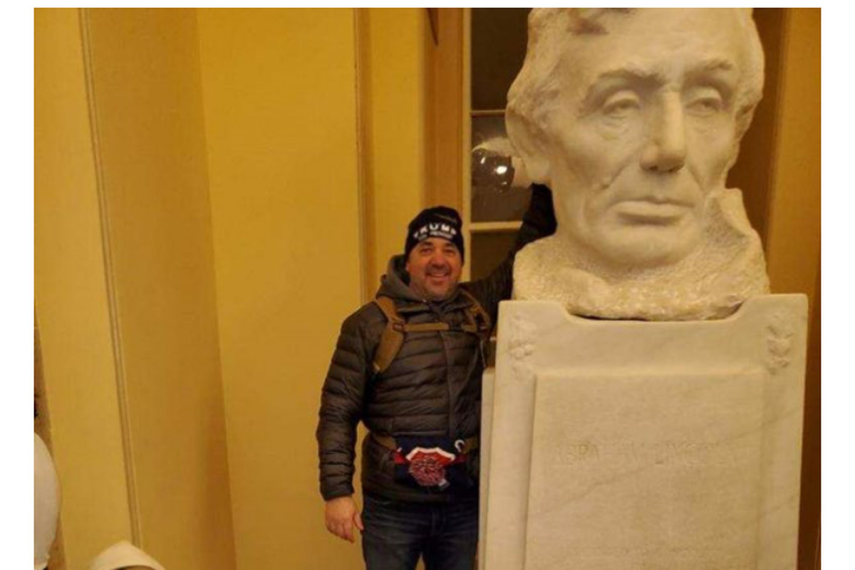 In a screenshot from Michael Hardin's federal complaint, a photo provided to the FBI by a tipster shows a man the tipster says is Hardin posing next to a bust of Abraham Lincoln in the Capitol Crypt on Jan. 6, 2021. The tipster told investigators they received the image from a relative of Hardin, who received it from Hardin directly.